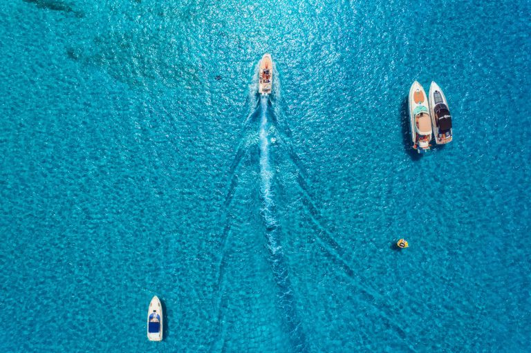 Aerial view of luxury yachts in transparent blue sea