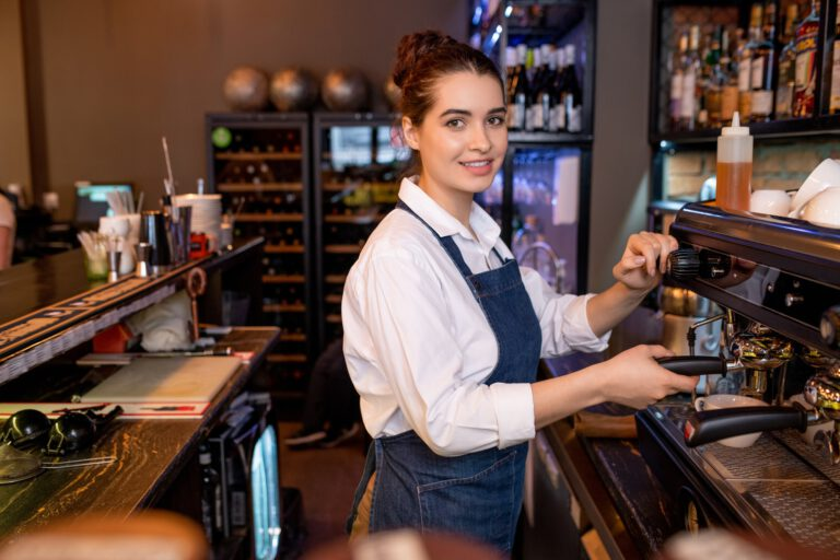 Young friendly waitress in workwear preparing cappuccino by coffee machine